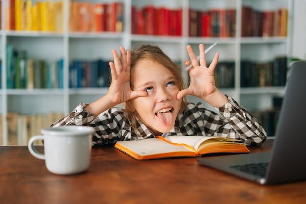 Zbliżenie z przodu szczęśliwy ładny uczeń dziecko uczennica wygłupiać się przy stole z laptopem i papierowym notatnikiem, patrząc na kamery. ładny uśmiechający się uczennica e-learningu online przy użyciu komputera.