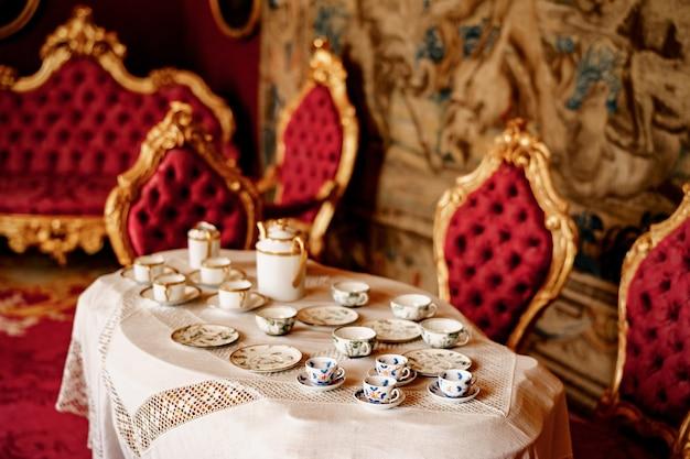 Zbliżenie z trzech rodzajów herbaty na stole z koronkowym obrusem i krzesłami ze złotymi obręczami i czerwonymi