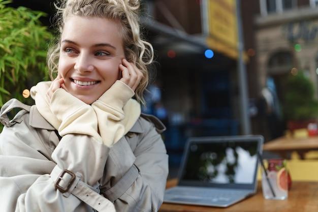 Zbliżenie z tyłu piękna blond dziewczyna odwraca się w aparacie siedząc stolik z laptopem i koktajl.