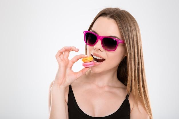 Zbliżenie zabawnej treści zadowolona młoda kobieta ciesząca się degustacją makaroników