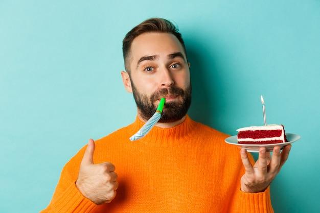 Zbliżenie: zabawny dorosły mężczyzna obchodzi swoje urodziny, trzyma tort urodzinowy ze świecą, dmuchanie gwizdkiem i pokazuje kciuk w górę, stojąc na jasnoniebieskim tle.