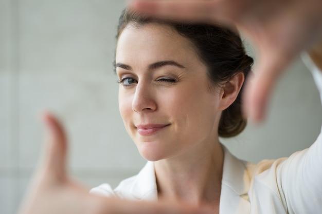 Zbliżenie zabawny kobieta podejmowania ramki i mrugająca