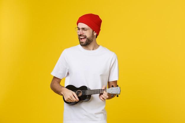 Zbliżenie zabawny młody człowiek gra na gitarze. samodzielnie na żółtym złocie