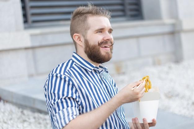 Zbliżenie: zabawny młody hipster facet jedzący chiński makaron z drewnianymi pałeczkami siedzi w parku na zewnątrz w ciepły letni dzień. pojęcie odpoczynku i podjadania na ulicy.