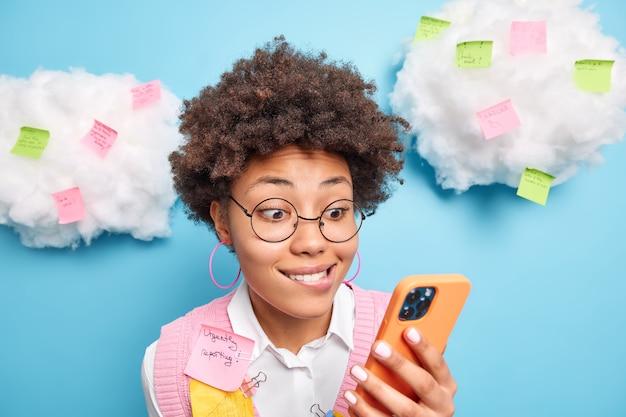 Zbliżenie zaciekawionej dziewczyny gryzie usta i patrzy z zainteresowaniem na ekran smartfona czyta treść wiadomości zajęty przygotowaniami do egzaminów ma wiele pilnych zadań robi notatki przypominające