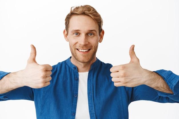 Zbliżenie zadowolonego szczęśliwego faceta pokazuje kciuki w górę i uśmiecha się, chwali coś dobrego, doskonałą robotę, komplementuj swój wysiłek, dobrze zrobione, doskonałe, stojąc nad białą ścianą