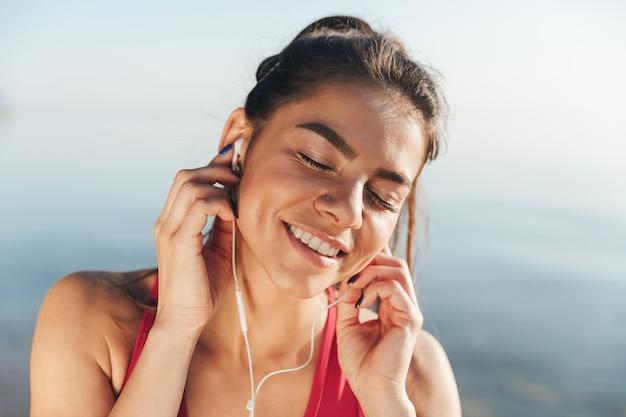 Zbliżenie zadowolony sportsmenka, słuchanie muzyki