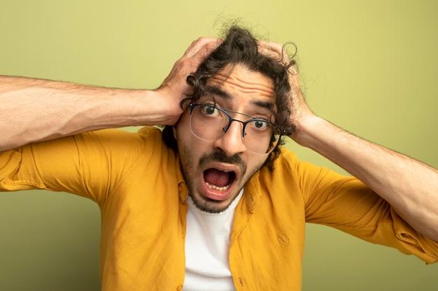 Zbliżenie zainteresowany młody przystojny mężczyzna w okularach trzymając głowę patrząc z przodu na białym tle na oliwkowej ścianie