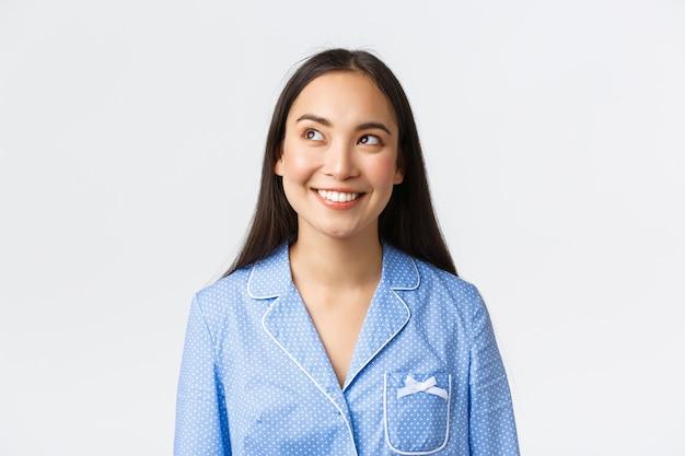 Zbliżenie zaintrygowanej, przemyślanej uroczej azjatki w niebieskiej piżamie, mającej pomysł, patrzącej z zadowolonym uśmiechem i białymi zębami w lewym górnym rogu, czytającej baner promocyjny, białe tło.
