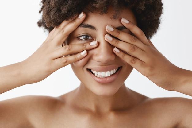Zbliżenie zalotnej, emocjonalnej i wspaniałej nagiej modelki o ciemnej karnacji z kręconymi włosami zakrywającymi oczy dłońmi i zerkającą przez palce, szeroko uśmiechnięta, czekająca na niespodziankę lub prezent