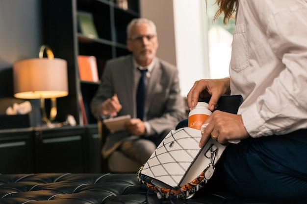 Zbliżenie zamężnych kobiet ręce trzymając pudełko leków przeciwdepresyjnych w biurze psychologów