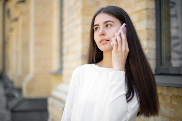 Zbliżenie: zamyślona brunetka dziewczyna w bieli z długimi włosami rozmawia przez telefon komórkowy, idąc ulicą. miejsce na twój projekt