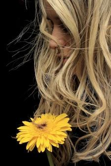 Zbliżenie zamyślona kobieta z żółtym kwiatem