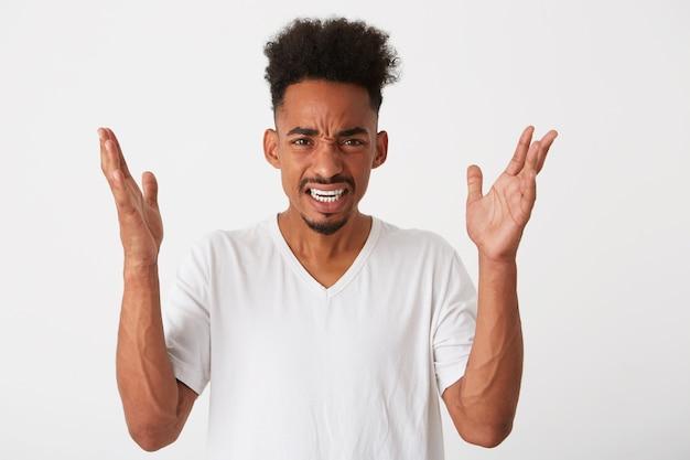 Zbliżenie zamyślonego atrakcyjnego młodego mężczyzny z kręconymi włosami i piegami nosi koszulkę, wygląda zamyślony i myśli na białym tle nad białą ścianą