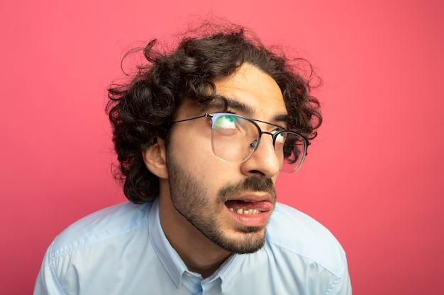 Zbliżenie zamyślony młody przystojny kaukaski mężczyzna w okularach pokazując język patrząc w górę na białym tle na szkarłatnej ścianie