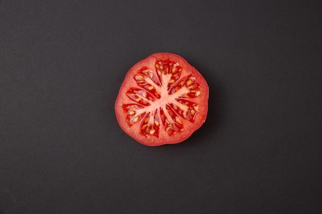 Zbliżenie zasięrzutny widok połówka rżnięty pomidor na abstrakcjonistycznym czarnym tle