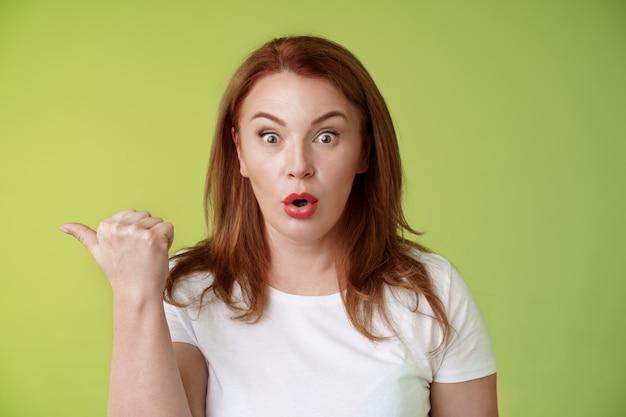 Zbliżenie zaskoczona rozbawiona rudowłosa gospodyni w średnim wieku, składająca usta, mówi: wow pod wrażeniem spojrzenie kamera przesłuchana zasadzka wskazująca lewy kciuk