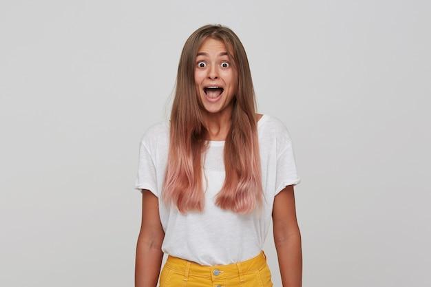 Zbliżenie zaskoczonej atrakcyjnej młodej kobiety z długimi farbowanymi pastelowymi różowymi włosami nosi koszulkę stojącą z otwartymi ustami i czuje się podekscytowana na białym tle nad białą ścianą