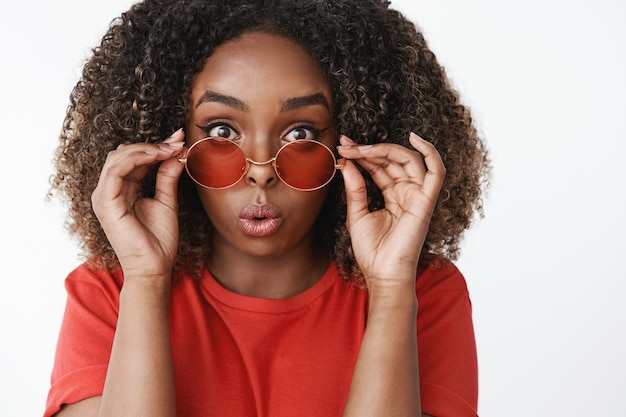 Zbliżenie zaskoczonej i rozbawionej atrakcyjnej afroamerykańskiej kobiety z kręconymi włosami, zdejmującej okulary przeciwsłoneczne i zaginającej usta ze zdumienia i zainteresowania reagującego na imponującą scenę