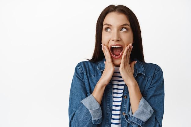 Zbliżenie zaskoczonej i zachwyconej dziewczyny krzyczącej ze zdumienia na białym?