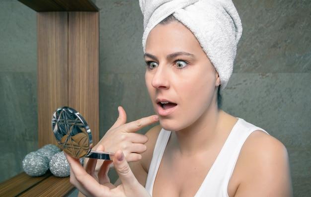 Zbliżenie zaskoczonej kobiety z ręcznikiem na włosach patrzącej w lustro z trądzikowym pryszczem na jej pięknej twarzy w łazience