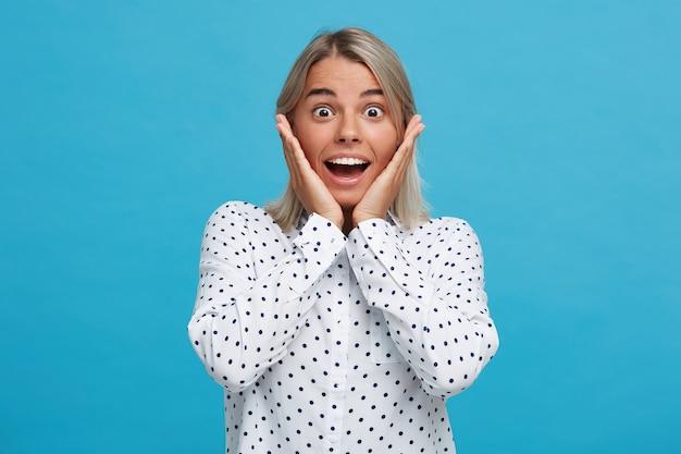 Zbliżenie zaskoczonej, podekscytowanej blondynki młodej kobiety z otwartymi ustami nosi koszulę w kropki, czuje się szczęśliwa, dotyka jej twarzy i wygląda na zdumionego odizolowaną na niebieskiej ścianie