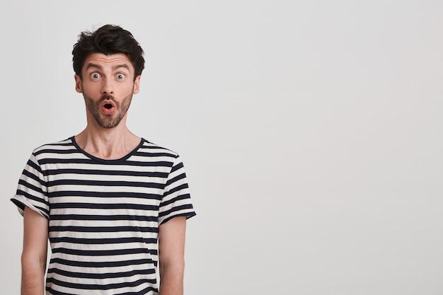 Zbliżenie zaskoczony przystojny młody człowiek z włosia nosi t shirt w paski, czuje się oszołomiony stojąc na białej ścianie