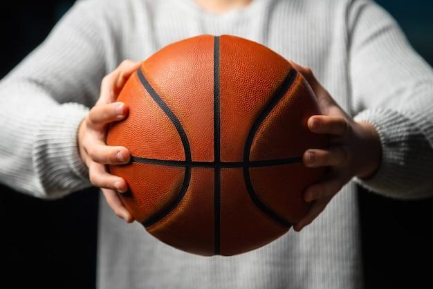 Zbliżenie zawodowy koszykarz trzymając piłkę w ręku.