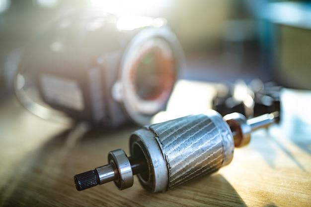 Zbliżenie zdemontowanego metalowego silnika z przewodem