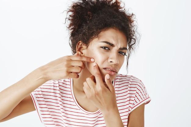 Zbliżenie zdenerwowanej kobiety z afro fryzury pozowanie w studio