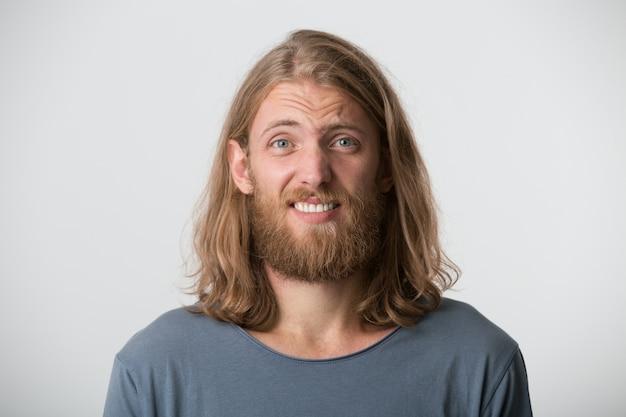 Zbliżenie zdezorientowanego smutnego młodzieńca z brodą i blond długimi włosami nosi szarą koszulkę, czuje się zawstydzony i zdenerwowany na białym tle nad białą ścianą