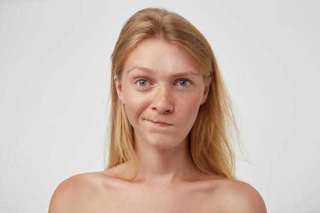 Zbliżenie zdezorientowanej młodej uroczej długowłosej kobiety z naturalnym makijażem wykręcającym usta i zdziwioną twarzą, odizolowanej na białej ścianie