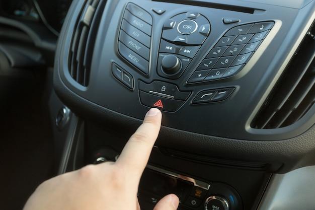 Zbliżenie zdjęcia kierowcy naciskającego przycisk awaryjny na desce rozdzielczej samochodu!
