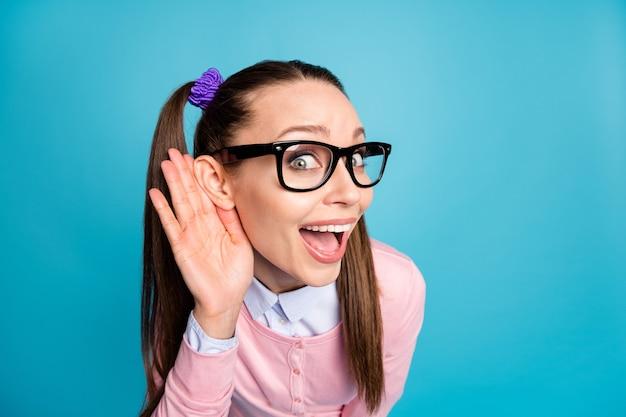 Zbliżenie zdjęcia zdumionej funky nastoletniej dziewczyny z college'u, trzymaj za rękę ucho, słuchaj niesamowitej plotki
