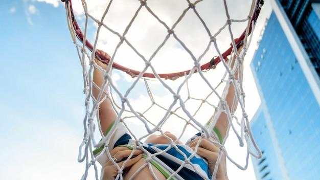 Zbliżenie zdjęcie aktywnych 3 lat chłopiec malucha, trzymając na pierścieniu netto koszykówki. koncepcja dzieci aktywnych i wysportowanych. zdrowie dzieci nowej generacji