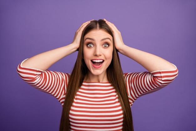Zbliżenie zdjęcie atrakcyjnej szalonej śmiesznej pani dobry nastrój długie fryzury otwarte usta ramiona na głowie słuchaj wspaniałych wiadomości nosić casualową koszulę w paski na białym tle pastelowy fioletowy kolor ściana