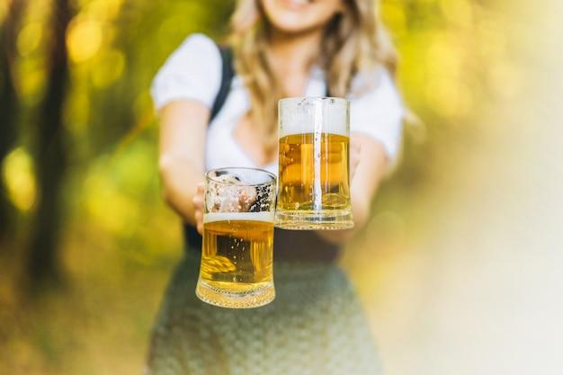Zbliżenie zdjęcie blondynki w dirndl, tradycyjnej sukience festiwalowej, trzymającej w rękach dwa kufle piwa