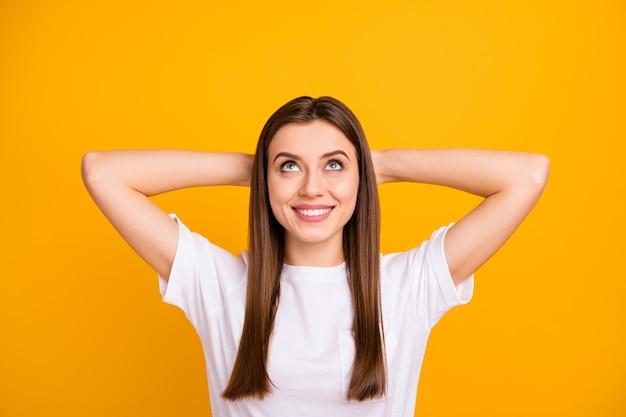 Zbliżenie zdjęcie całkiem spokojnej pani dobry nastrój myśli patrząc w górę pustej przestrzeni ramiona za głową zachwycony ząbkowaty nosić dorywczo biały t-shirt na białym tle żywy żółty kolor ściany