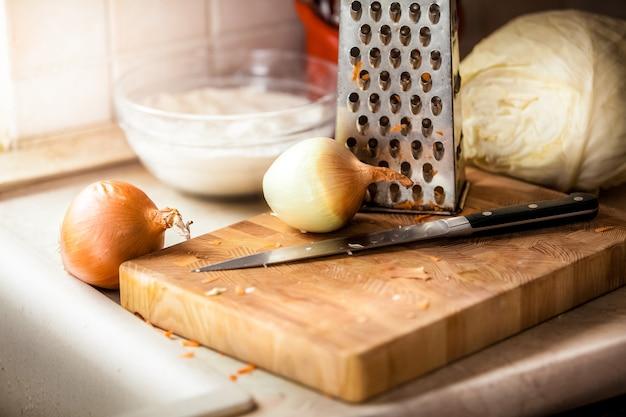 Zbliżenie zdjęcie cebuli i noża leżące na drewnianej desce