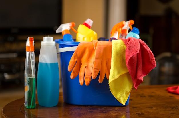 Zbliżenie zdjęcie chemikaliów czyszczących, rękawiczek i szmat leżących w plastikowym wiadrze