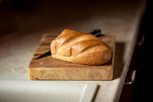 Zbliżenie zdjęcie chleba i noża na drewnianym biurku