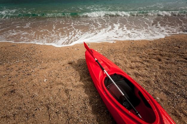 Zbliżenie zdjęcie czerwonego kajaka na pięknej, piaszczystej plaży w błękitne faliste morze