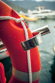 Zbliżenie zdjęcie czerwonego koła ratunkowego z liną przeciwko portowi morskiemu