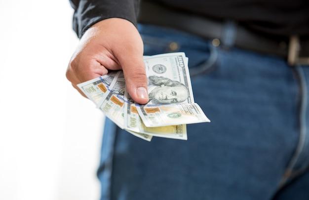 Zbliżenie zdjęcie człowieka pokazującego rękę z banknotami stu dolarowymi