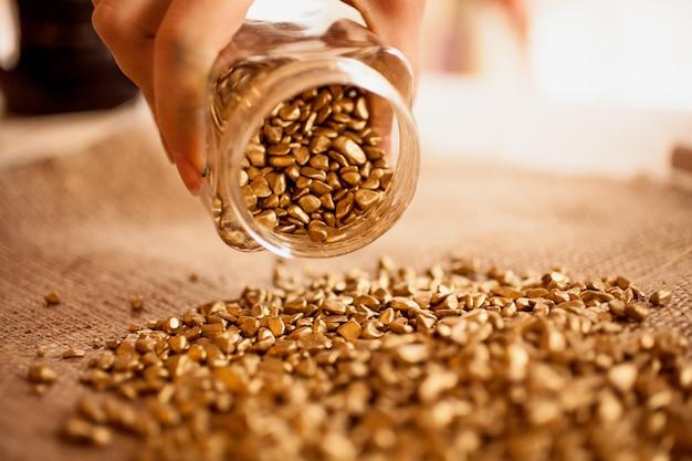Zbliżenie zdjęcie człowieka wylewającego słoik pełen złotych samorodków