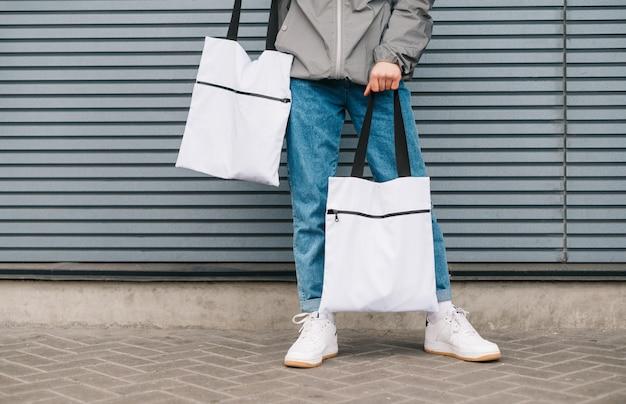 Zbliżenie zdjęcie dna stylowego mężczyzny w ubranie, trzymając białe torby eco w ręku