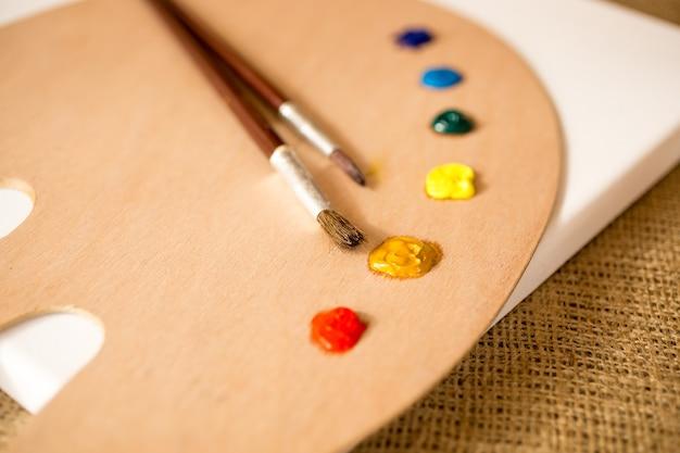 Zbliżenie zdjęcie drewnianej palety, pędzli i plamy farby olejnej