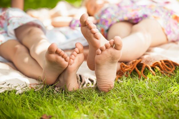 Zbliżenie zdjęcie dwóch sióstr stóp leżących na trawie w parku