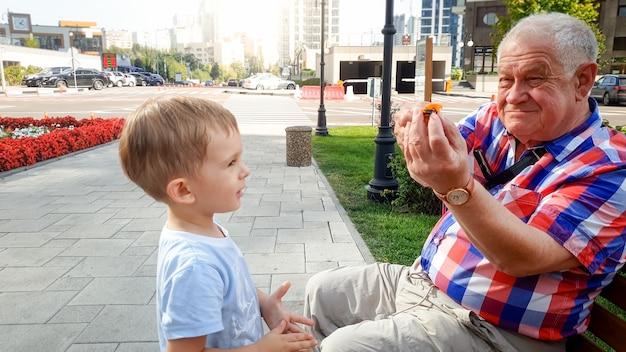 Zbliżenie zdjęcie dziadka bawiącego się z wnukiem małego dziecka w parku