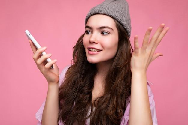 Zbliżenie zdjęcie emocjonalnej atrakcyjnej młodej kobiety brunetka ubrana w stylową różową koszulę i szary kapelusz